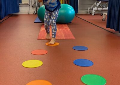 child having fun running during treatment in a specialist physiotherapy session improving balance and co- ordination