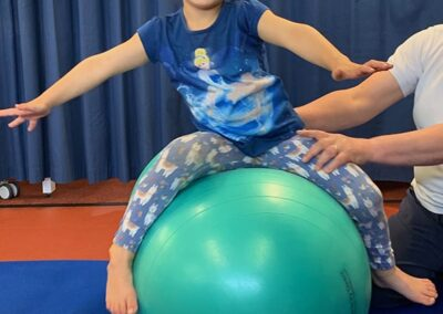 Having fun during advanced balance practice in Physio for child with dyspraxia, developmental co-ordination disorder